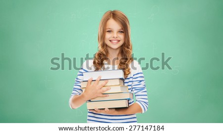education, people, children and school concept - happy little student girl with many books over green board background - stock photo