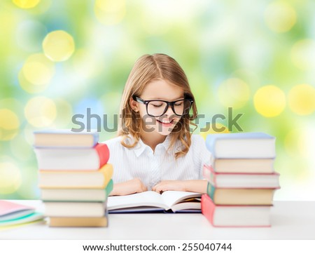 education, people, children and school concept - happy student girl in eyeglasses reading book over green lights background - stock photo