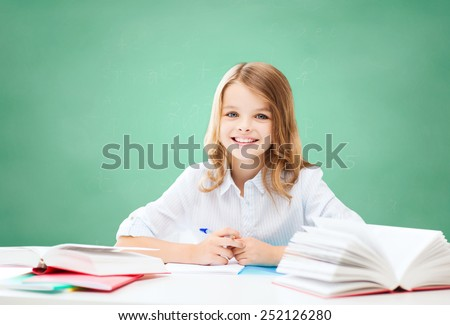 education, people, children and school concept - happy student girl sitting at table with books and writing in notebook over green chalk board background - stock photo