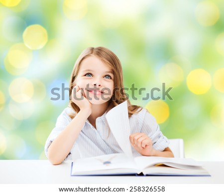 education, people, children and school concept - little student girl sitting at table with book over green lights background - stock photo