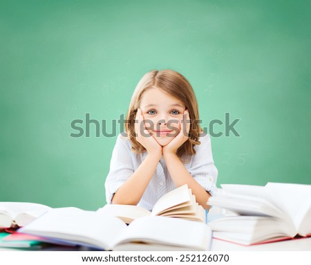 education, people, children and school concept - little student girl sitting at table with books over green chalk board background - stock photo