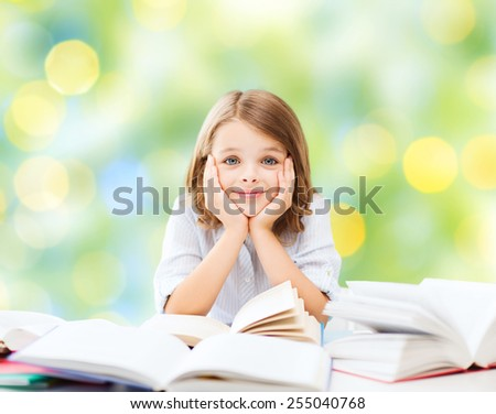 education, people, children and school concept - little student girl sitting at table with books over green lights background - stock photo