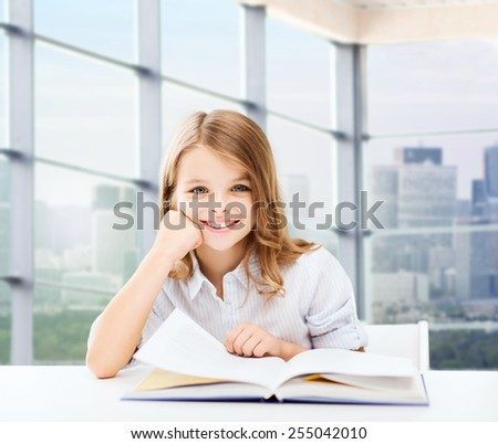 education, people, children and school concept - little student girl sitting at table with books and writing in notebook over classroom background - stock photo