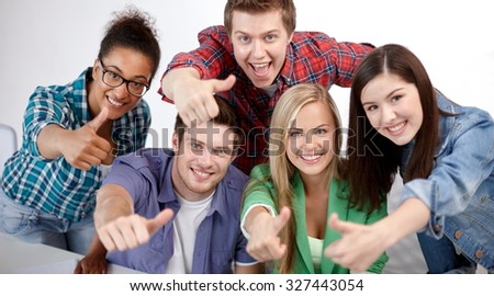 education, people, friendship and learning concept - group of happy international high school students or classmates showing thumbs up - stock photo