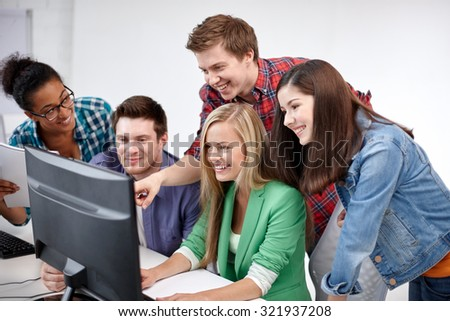 education, people, friendship, technology and learning concept - group of happy international high school students or classmates in computer class - stock photo