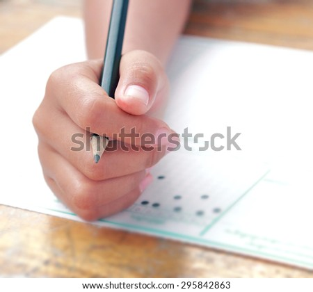 Education person hand on examination answer sheet with black pencil in finger shot with wide aperture