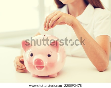 education, school and money saving concept - smiling child putting coin into big piggy bank - stock photo