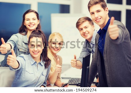education, school and people concept - students with computer monitor and smartphones showing thumbs up - stock photo