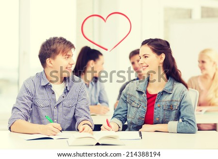 education, school and people concept - two teenagers with notebooks and book looking at each other at school - stock photo