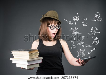 Education school and technology concept. Surprised nerd student with old books in one hand and e-reader in another on grey background.  - stock photo
