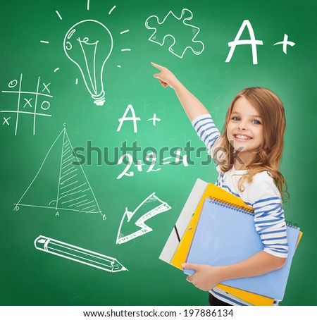 education, school and virtual screen concept - cute little girl with colorful folders pointing to green board - stock photo