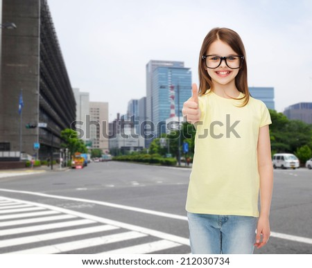 education, school and vision concept - smiling cute little girl in black eyeglasses showing thumbs up - stock photo
