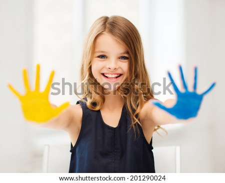education, school, art and happiness concept - little student girl showing hands in yellow and blue color at school - stock photo