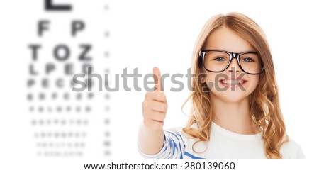 education, school, childhood, people and vision concept - smiling cute little girl with black eyeglasses showing thumbs up gesture over eye chart background - stock photo