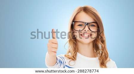 education, school, childhood, people and vision concept - smiling cute little girl with black eyeglasses showing thumbs up gesture over blue background - stock photo
