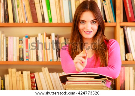 Education school concept. Happy female student fashion long hair girl in college library with stack books making research pointing with pen