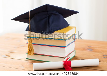 education, school, graduation and knowledge concept - close up of books and mortarboard with diploma on wooden table - stock photo