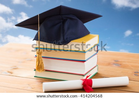 education, school, graduation and knowledge concept - close up of books and mortarboard with diploma on wooden table over blue sky and clouds background - stock photo