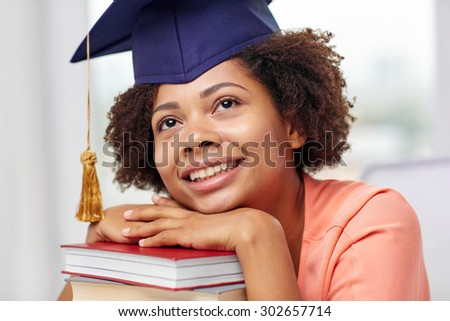education, school, knowledge, graduation and people concept - happy smiling african american student girl in bachelor cap with books sitting at table and dreaming at home - stock photo