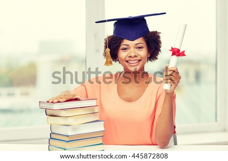 education, school, knowledge, graduation and people concept - happy smiling african american student girl in bachelor cap with books and diploma sitting at table at home - stock photo