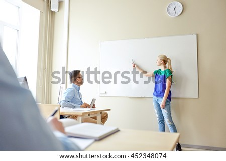 education, school, learning and people concept - student girl showing something on blank white board and teacher in classroom - stock photo