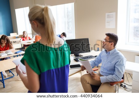 education, school, learning, examination and people concept - student boy with notebook and teacher in classroom - stock photo