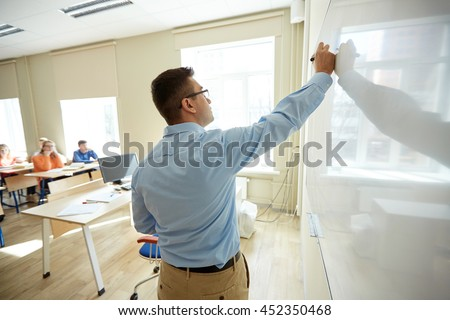 education, school, learning, teaching and people concept - teacher standing in front of students and writing something on white board in classroom - stock photo