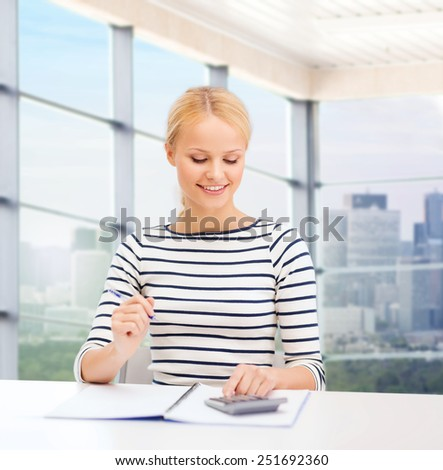 education, school, people and business concept - smiling woman with notebook and calculator over office window background - stock photo