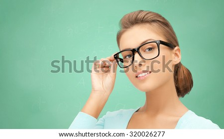 education, school, people and vision concept - happy teenage student girl or woman in eyeglasses over green school chalk board background
