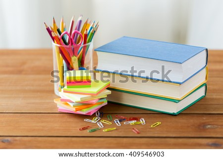 education, school supplies and object concept - close up of stand or glass with writing tools and book with scissors on wooden table