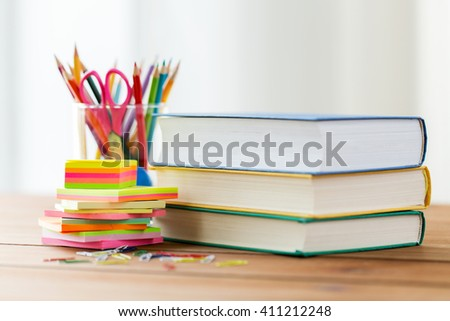 education, school supplies, and object concept - close up of stand or glass with writing tools and book with scissors on wooden table