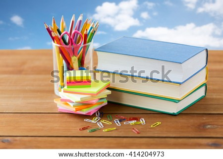 education, school supplies and object concept - close up of stand or glass with writing tools and book with scissors on wooden table over blue sky and clouds background