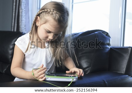 education, school, technology and internet concept - little girl with tablet pc - stock photo