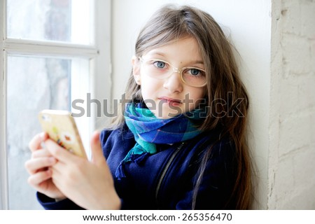education, school, technology and internet concept - little student girl with smartphone at home - stock photo