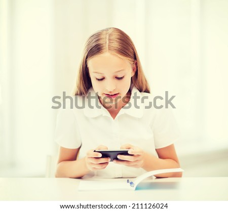 education, school, technology and internet concept - little student girl with smartphone at school - stock photo