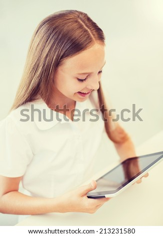 education, school, technology and internet concept - smiling little student girl with tablet pc computer at school