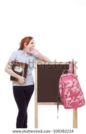 education series - Friendly Caucasian female high school student with backpack by blank blackboard with copy space - stock photo