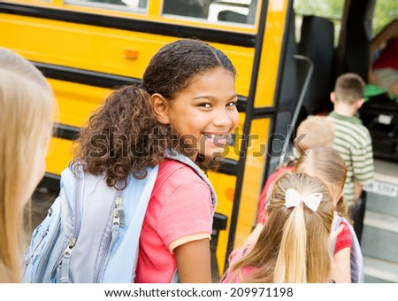 Education: Smiling Elementary Student Ready To Board Bus - stock photo