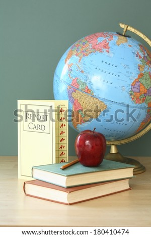 education still life with report card, apple, books, pencil, and globe  - stock photo