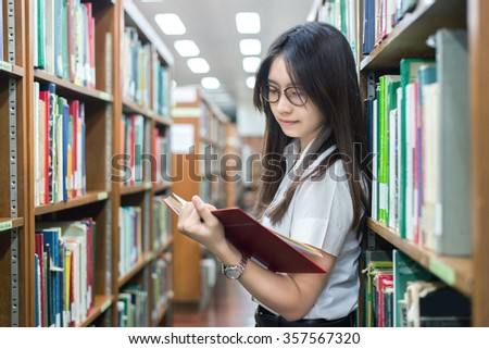 Education, Student, People concept - Asian student in uniform reading in the library at university. Asian student looking happy to read book.  - stock photo