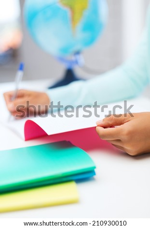 education, study, school and people concept - close up of young woman writing in workbook at school or home - stock photo