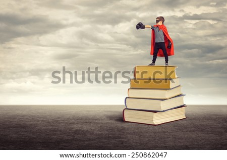 Education. Super hero boy standing on a pile of books in the open air.