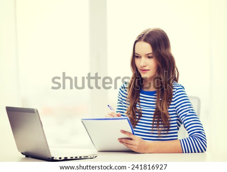 education, technology and home concept - concentrated teenage girl with laptop computer, notebook and pen at home