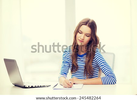 education, technology and home concept - concentrated teenage girl with laptop computer, notebook and pen at home - stock photo