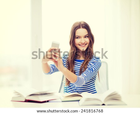 education, technology and home concept - happy smiling student girl with smartphone and books at home - stock photo