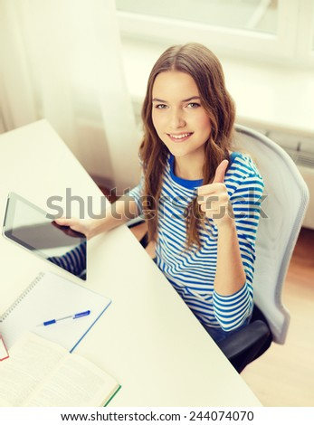 education, technology and home concept - happy smiling student girl with tablet pc computer and books at home - stock photo