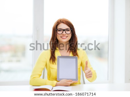 education, technology and internet concept - smiling student girl in eyeglasses with tablet pc at school showing thumbs up - stock photo