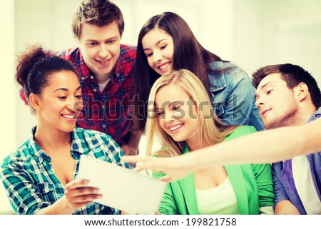education, technology and internet concept - smiling students looking at tablet pc at school