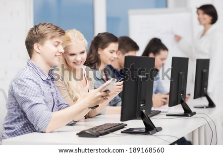 education, technology and internet concept - students with computer monitor and smartphones