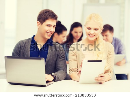 education, technology and internet concept - two smiling girl students with laptop and tablet pc at school